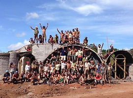 Many people working together to build a home/Earthship