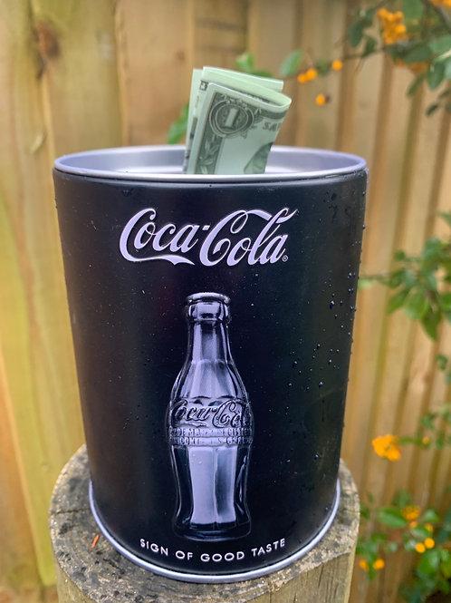 Coca Cola savings tin with dollar bill