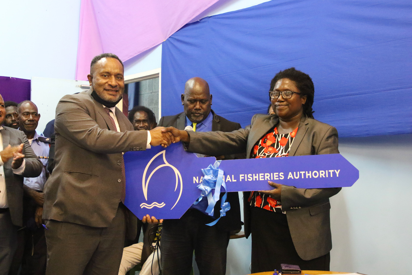 The Minister for Fisheries and Marine Resources, Hon. Dr Lino Tom presenting a key for a duplex accommodation for Fisheries officers in Buka