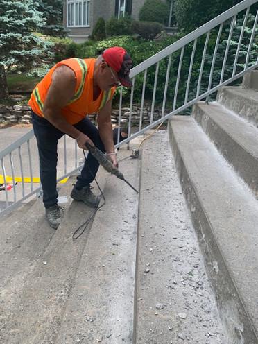 Andre Tremblay en train de réparer le beton