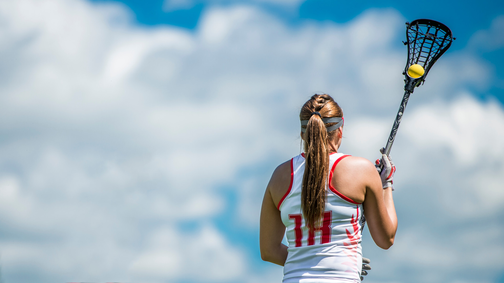 Women's lacrosse player against  the sky