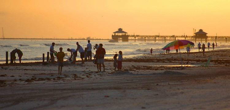 People on Fort Myers Beach with Fort Myers Beach Pier in the background
