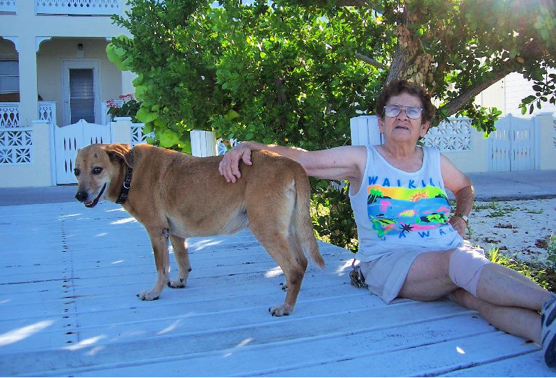 Shirley Roberts lounging outside of her Shell Hut gift shop with her dog