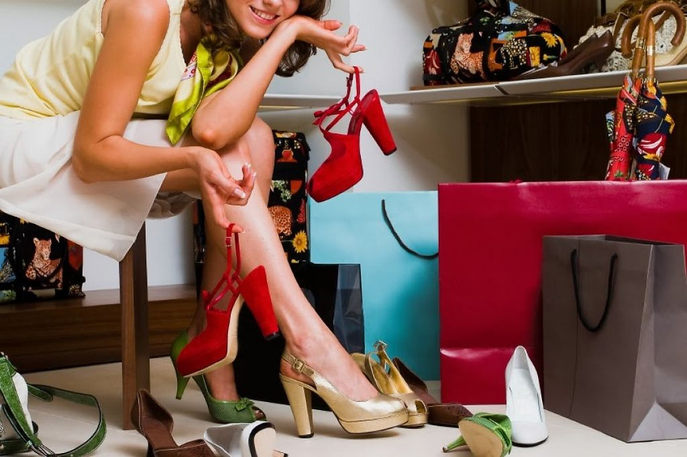 Woman with shoes and shopping bags, deciding what to pack