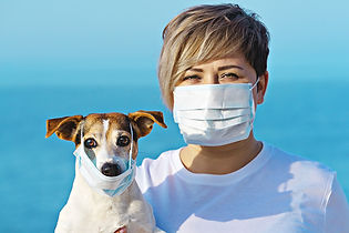 Woman and dog both wearing COVID-19 masks at beach