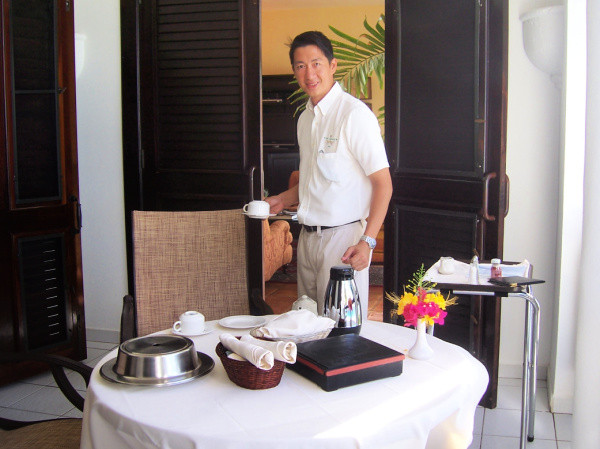 Our butler serving us breakfast on our balcony