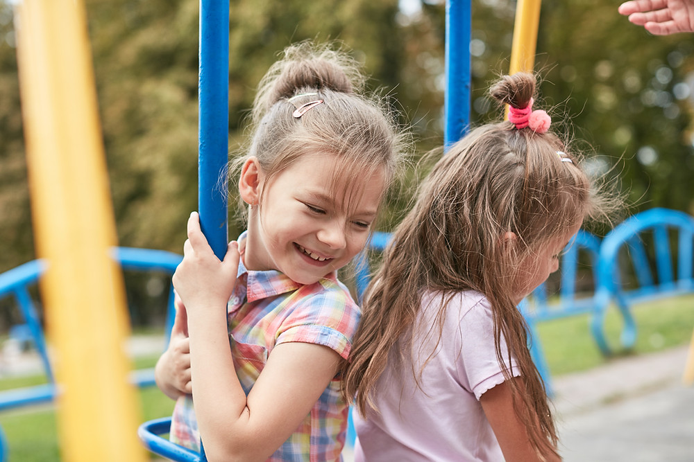 two girls playing on playground in park forest