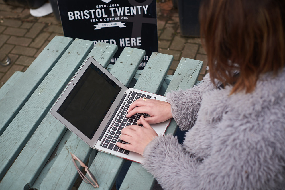 Woman on her laptop outside at a coffee shop in Bristol