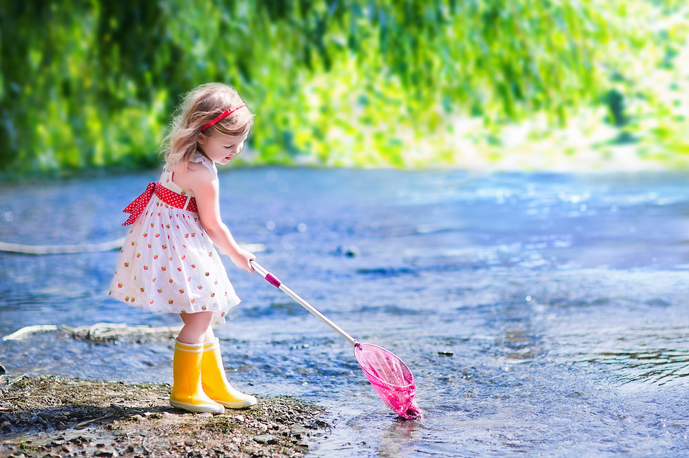 Little girl with a pink fishing rod in the water