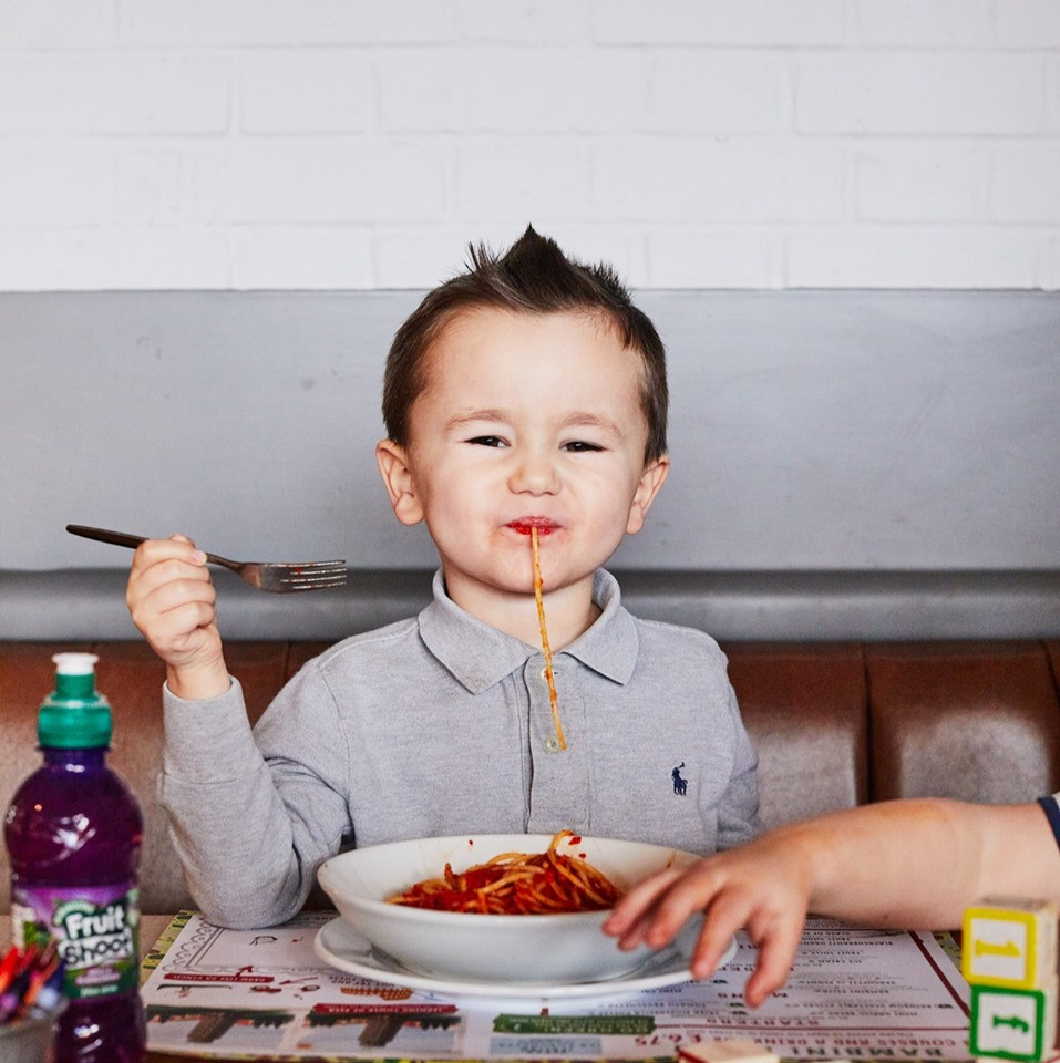 Young boy eating spaghetti bolognese