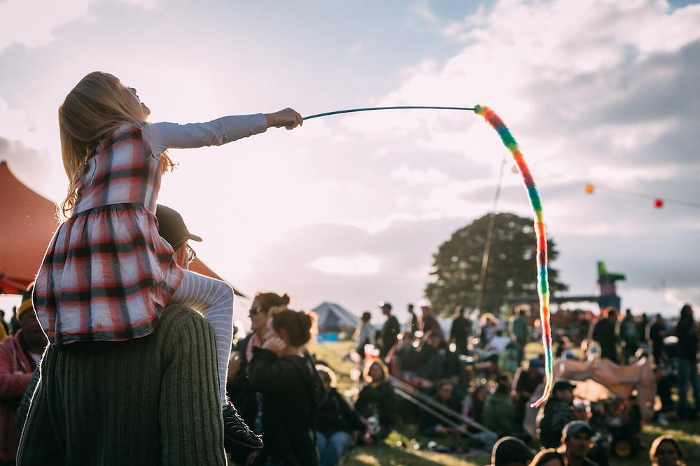 Girl on dad's shoulders enjoying a festival
