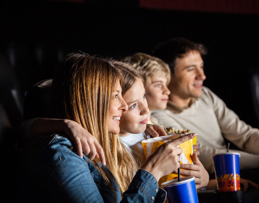 Family eating popcorn at the cinema.