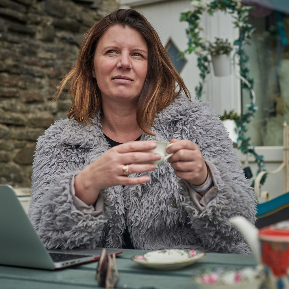 Ms Broke in Bristol drinking tea and working from her laptop