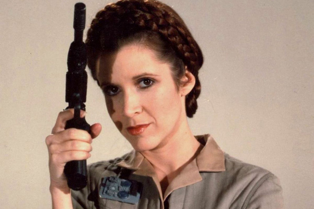 Carrie Fisher as Princess Leia with a blaster