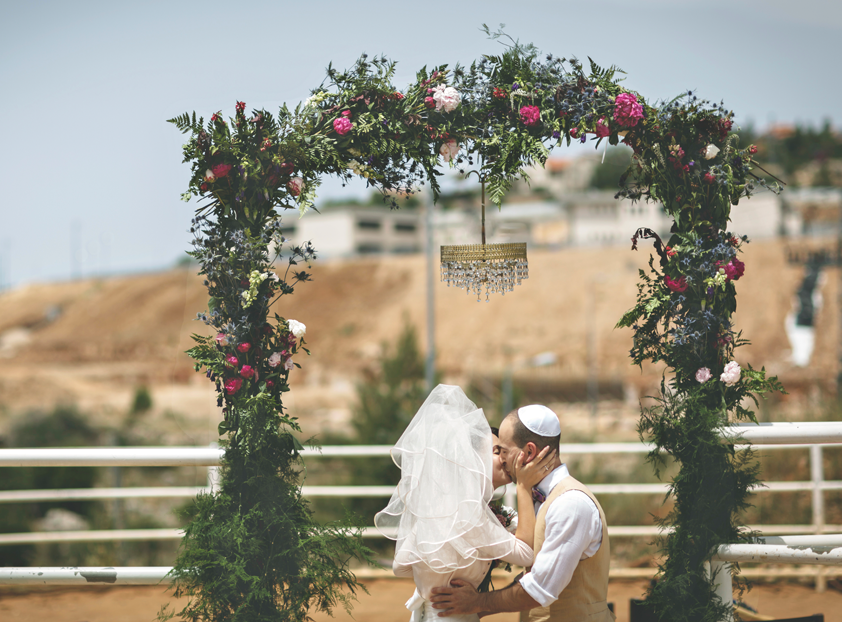 Wedding-Arch-Bride-Kissing-Groom