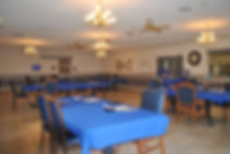 Diningroom with blue table cloths located next to the kitchen