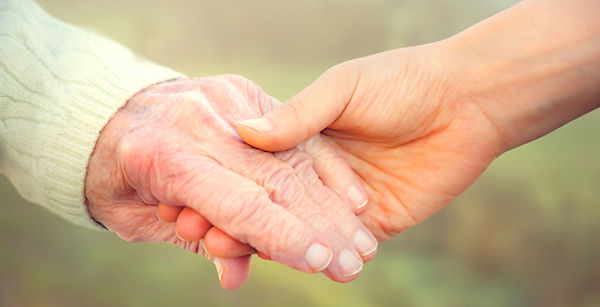 Elderly-person-holding-hands-with-younge