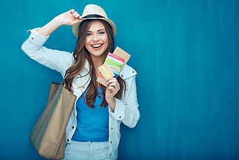 Smiling woman traveler holding passport with ticket and credit card. Blue wall back..jpg