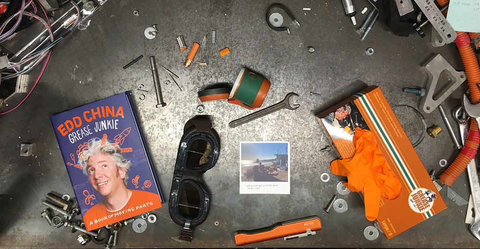 Edd China's workbench, covered in the usual detritus such as his book, his orange gloves, flying goggles and a Philips Penlight torch