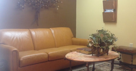 Lima Ohio dental office beautiful reception room decor featuring bronze magazine rack, leather couch and stone coffee table with Bible and other books