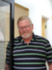 Lima Ohio dentist Gordon Rauch DDS picture taken next to a bookcase containing his daughter's dental themed art work