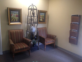 Lima Ohio dental office reception room decor with two comfy chairs, bronze colored magazine rack and paintings of landscapes