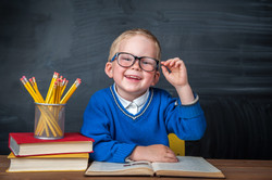 Happy cute clever boy is sitting at a desk in a glasses with raising hand. Child is ready to answer