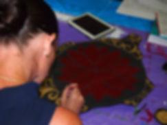 Women's Art Group participant finishing her artwork