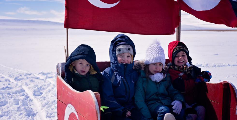 Happy Kids On A Horse Drawn Sleigh Ride Over Lake Cildir