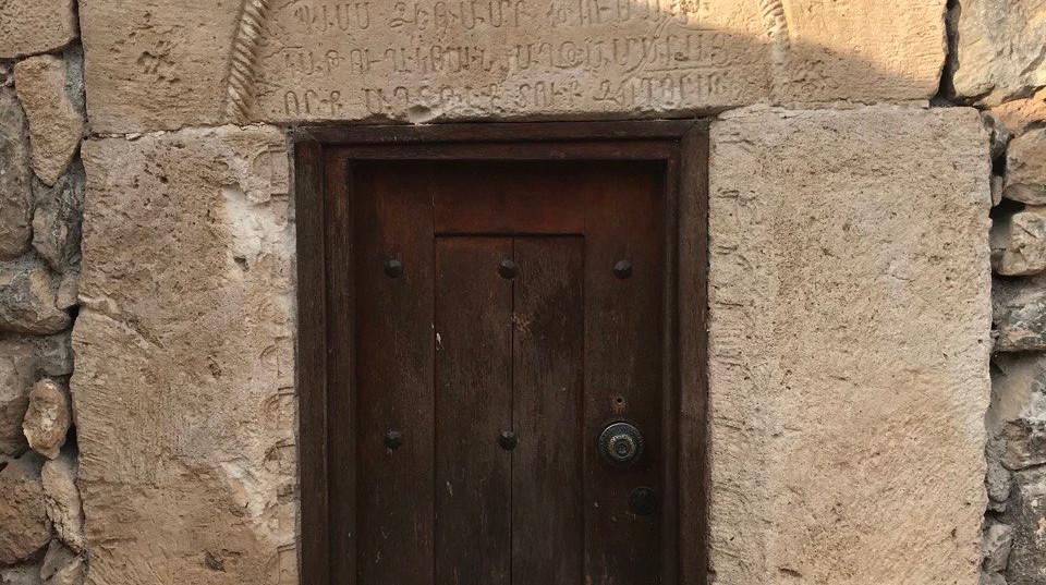 Old Door With Ancient Scripture Above It