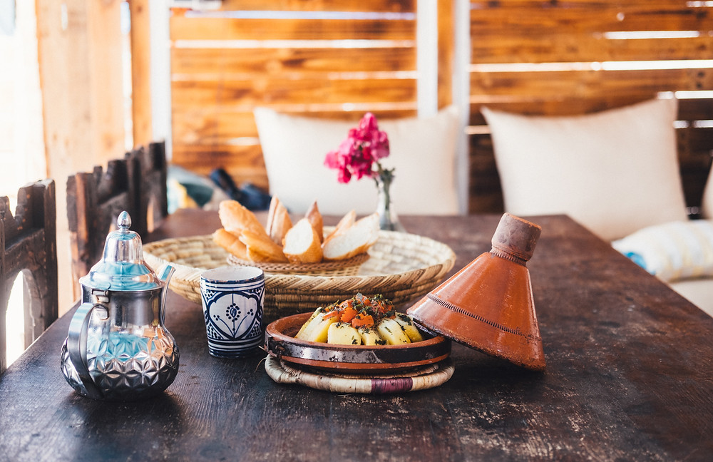 A Moroccan tajine rests next to a traditional pot of mint tea