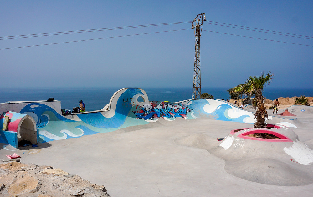 Painted blue waves cover the concrete walls of a skatepark overlooking the sea