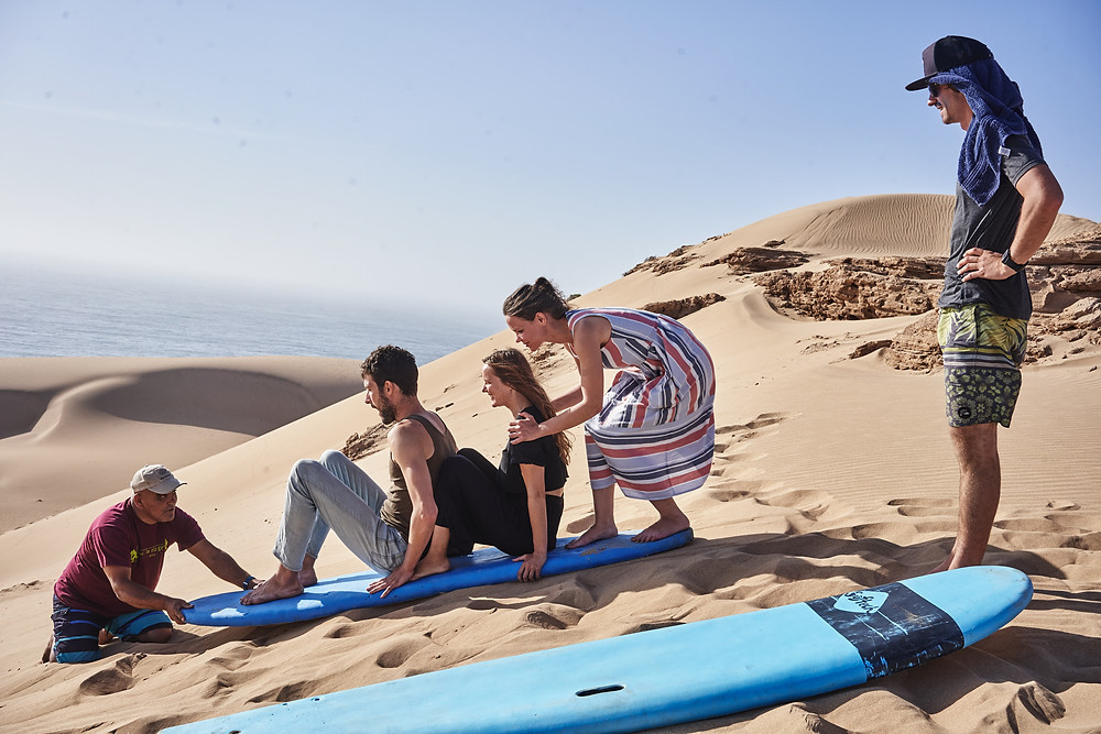 A man and women preparing to slide down a large sand dune on a surf board