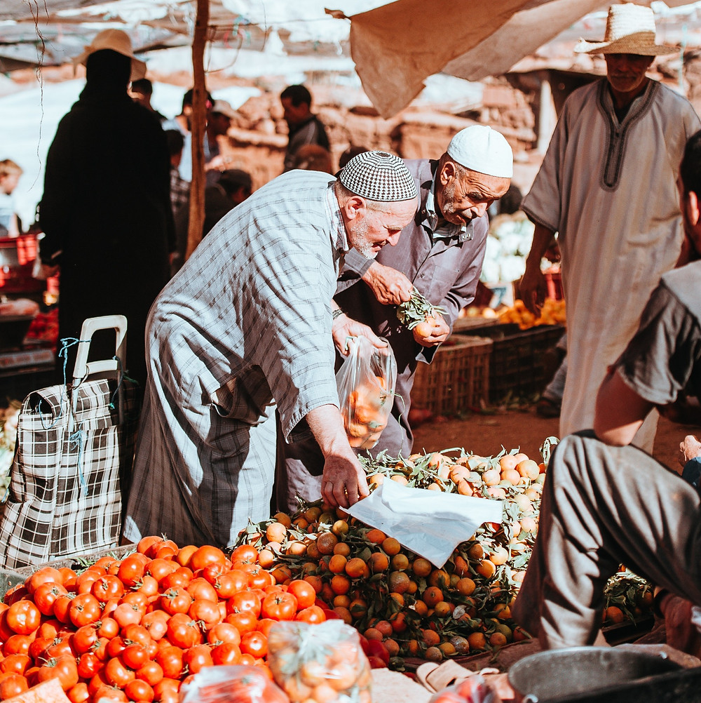 Two men carefully choose vegetables at a stand in a crowded market