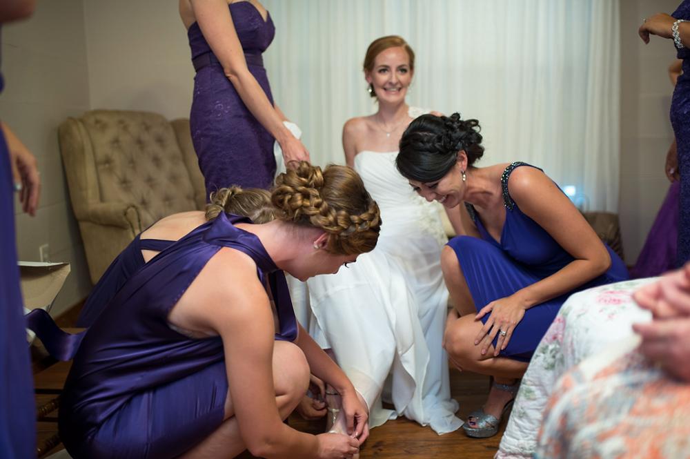 bridesmaids putting on brides shoes