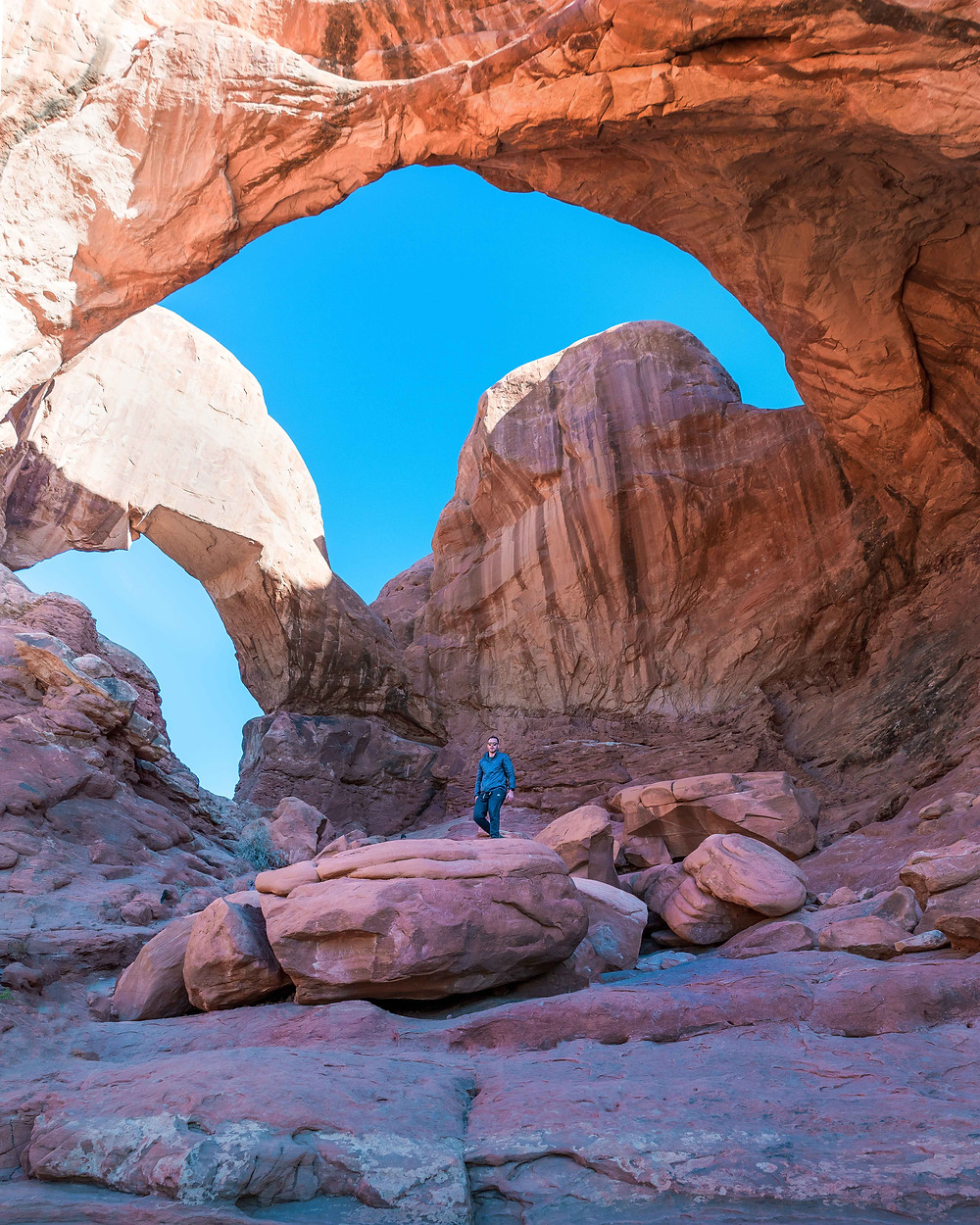 hiker standing under the double arch in arches national park
