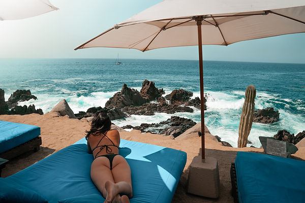 Girl laying on a sun chair next to the vivid blue Cabo San Lucas Ocean