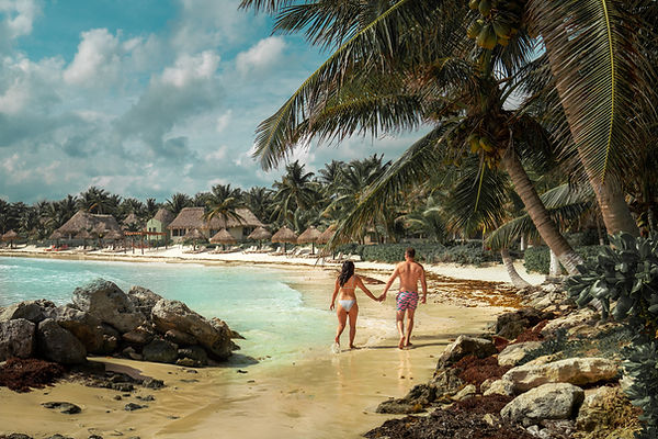 Travel Couple holding hands and strolling down a private beach in Tulum
