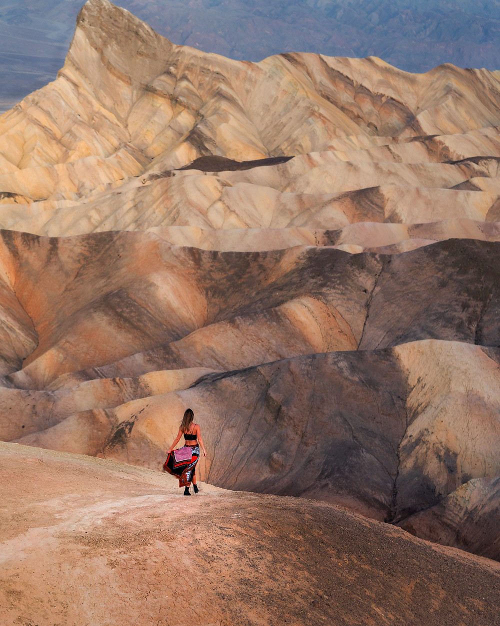 hiker in floral dress at the top of the vista at Zabriskie point