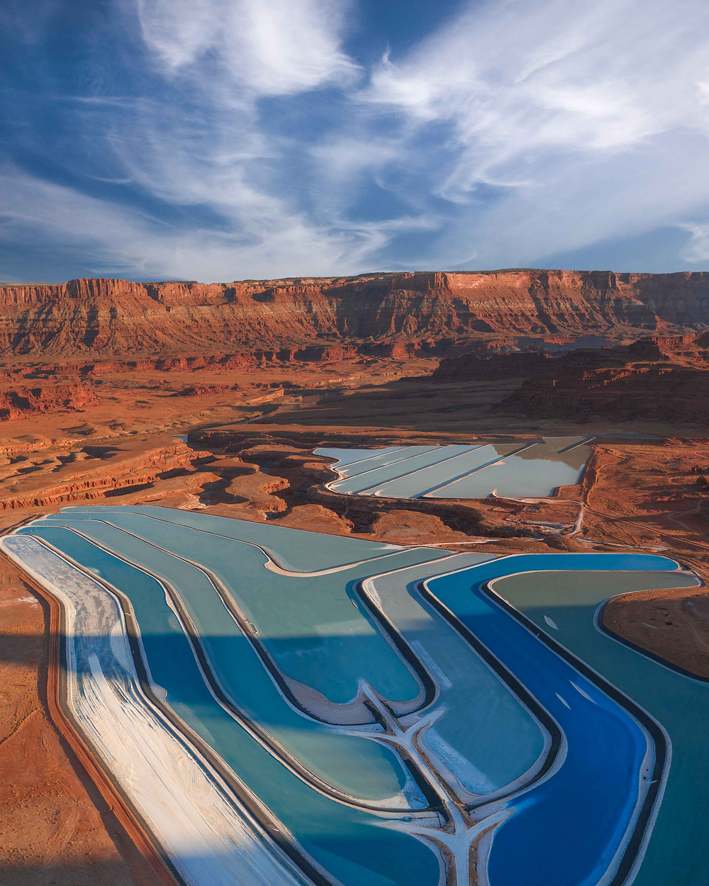 vibrant blue and white salt ponds on the canyon floor of the surrounding red rock mountains