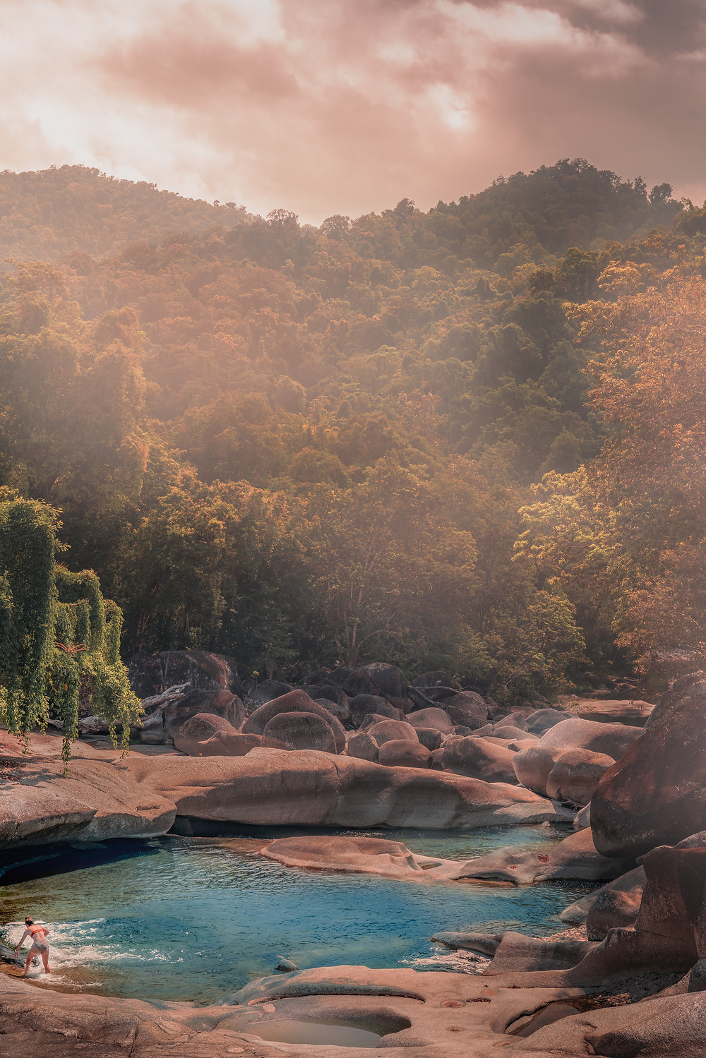 Bikini girl dipping in to the blue water of babinda boulders on a hot summer day