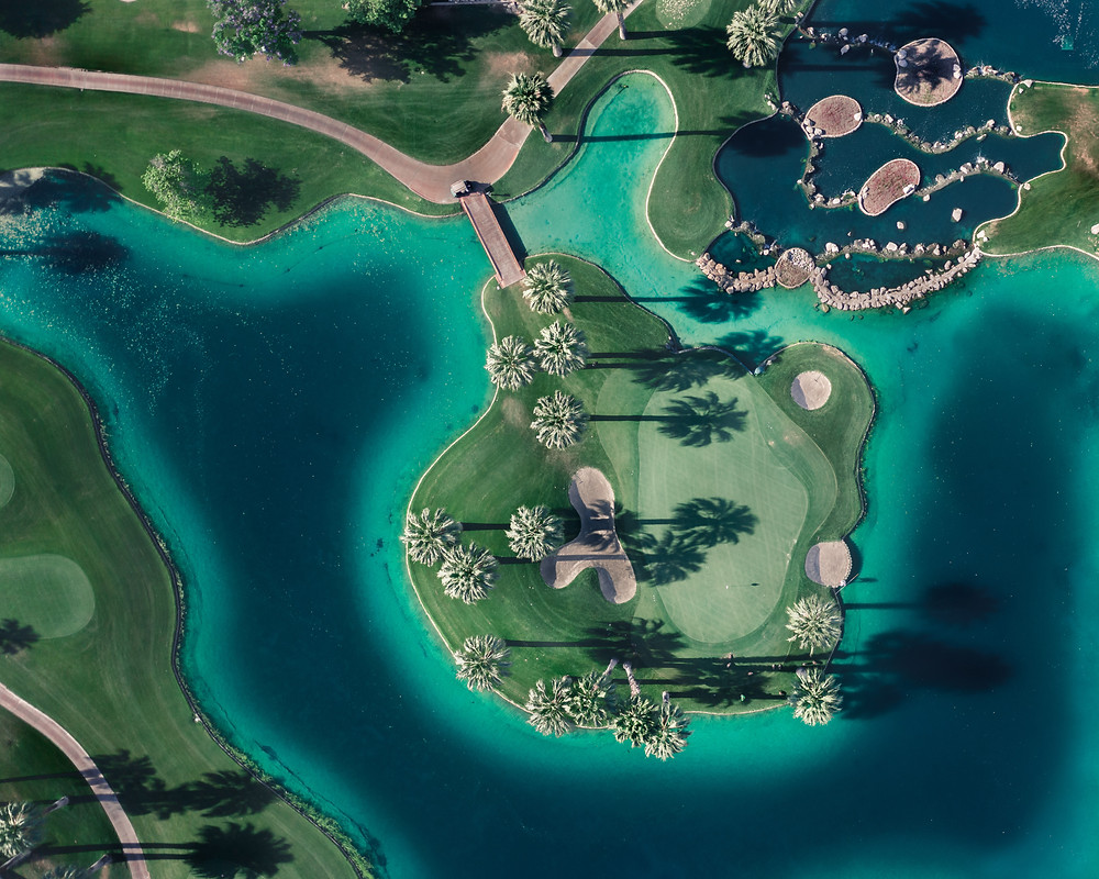 Aerial view of a golf course with palm tree shadows and beautiful surrounding water