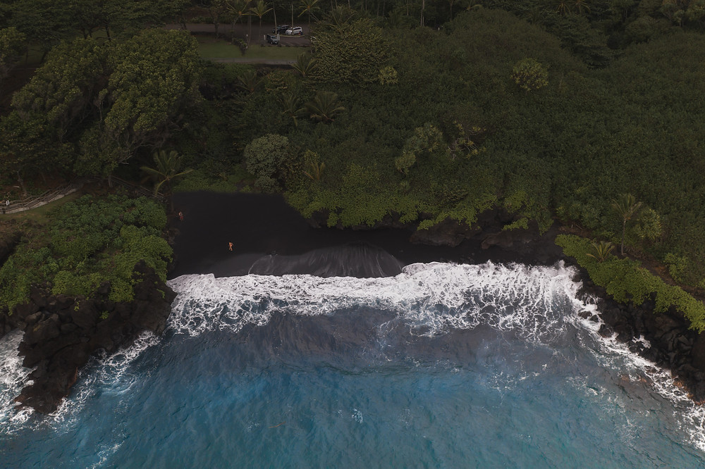 Aerial view of the black sand beach, lush green jungle, and blue ocean water in Hawaii