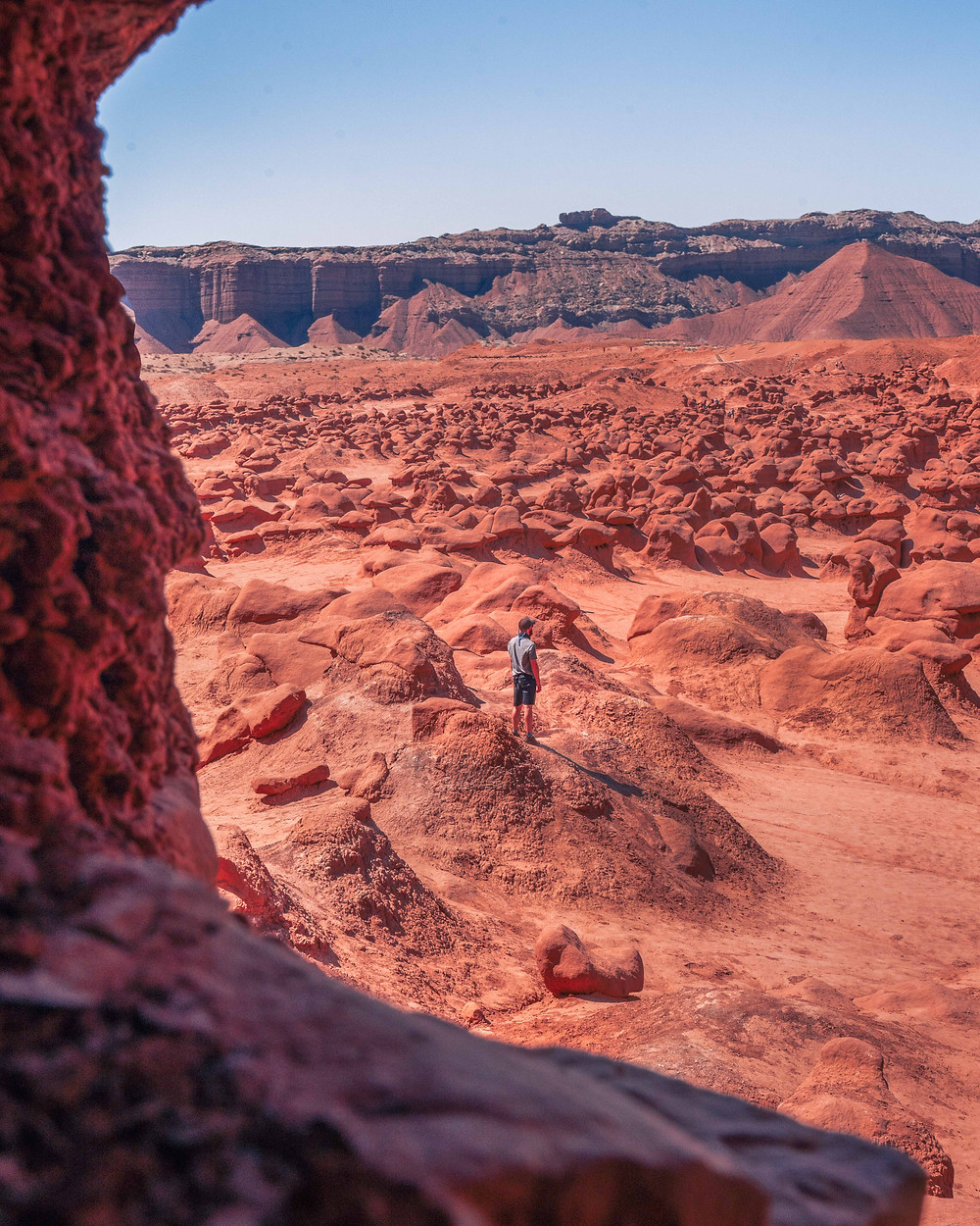 hiker in the middle of the red rock structures in Utah