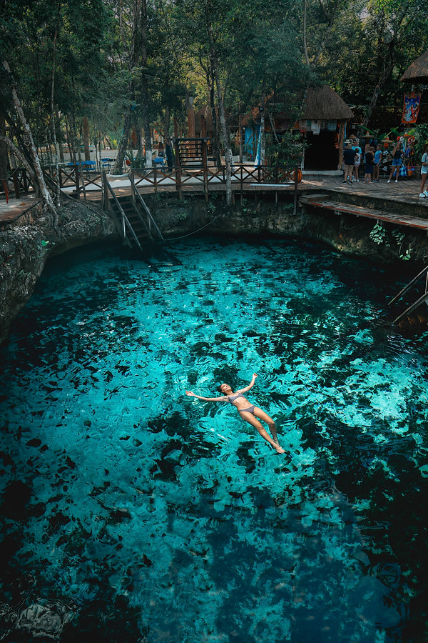Bikini model floating in a cenote