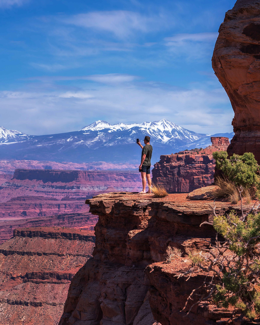 Man taking a photo of the red and purple rock and snow capped mountains in Canyonlands National Park