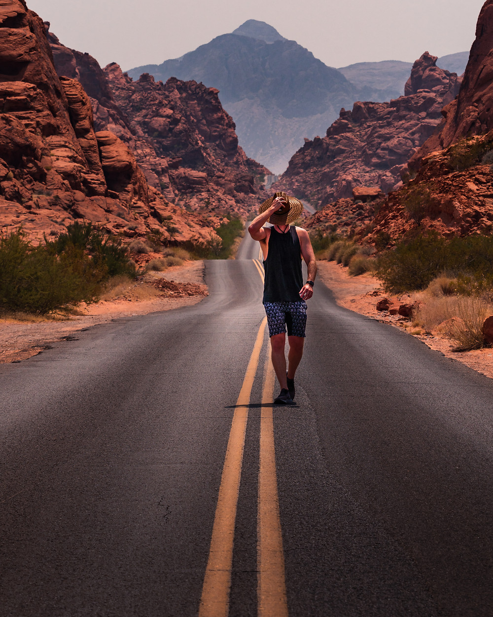 man walking through the desert heat with a hat in the valley of fire