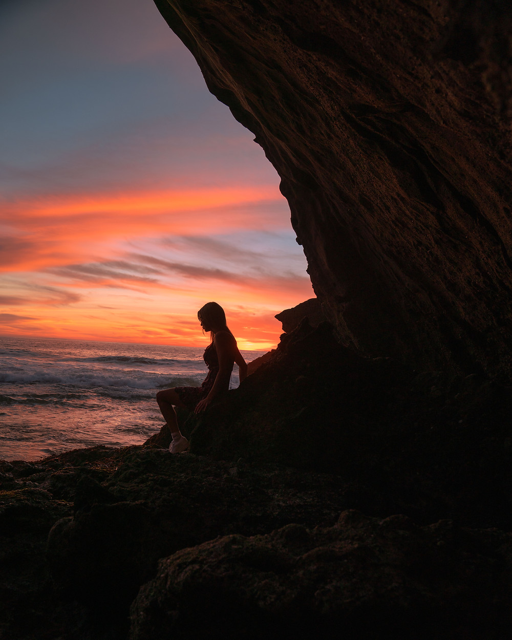Woman posing in a sea cave in front of an ocean sunset