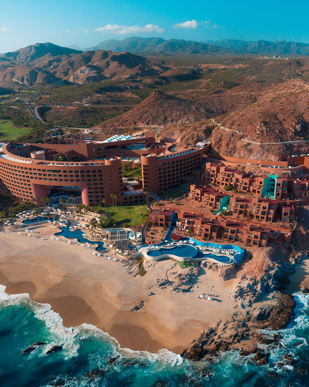 Aerial View of beach front Westin resort in front of desert mountain ranges