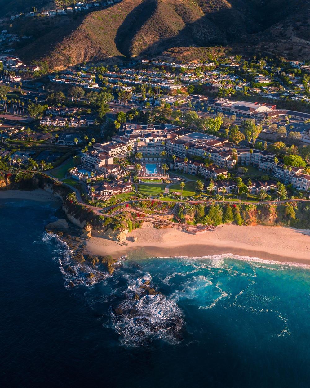 Vibrant aerial view of the ocean and stunning montage laguna hotel sitting on the beachside cliff